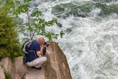 Uomo che fotografa una cascata Fotografia Stock