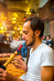 Uomo che fuma narghilé turco Immagine Stock
