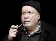 Uomo che fuma un tubo Fotografia Stock