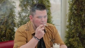Uomo che fuma una sigaretta alla tavola stock footage