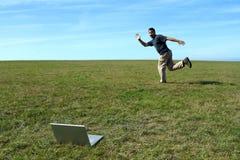 Uomo che funziona nel campo vicino al computer portatile Fotografia Stock Libera da Diritti