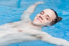 Uomo che galleggia nello stagno Fotografie Stock