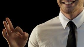 Uomo che gesturing okay isolato contro fondo nero video d archivio