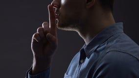 Uomo che gesturing silenzio isolato su nero, teorie di cospirazione, concetto top-secret stock footage