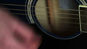 Uomo che gioca alto vicino della chitarra acustica video d archivio