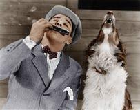 Uomo che gioca armonica con il cane di urlo (tutte le persone rappresentate non sono vivente più lungo e nessuna proprietà esiste Fotografia Stock Libera da Diritti