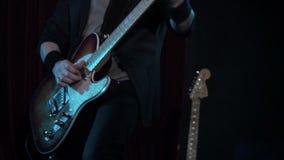 Uomo che gioca canzone della roccia sulla chitarra elettrica in night-club Primo piano Chitarra elettrica di legno del gioco del  video d archivio