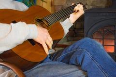 Uomo che gioca chitarra in Front Of Fire Fotografia Stock Libera da Diritti