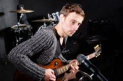 Uomo che gioca chitarra nella stanza scura Immagini Stock Libere da Diritti
