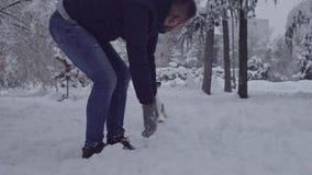 Uomo che gioca con il cane del terrier di russell della presa in allegro felice del cucciolo della neve video d archivio