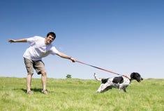 Uomo che gioca con il suo cane Fotografie Stock
