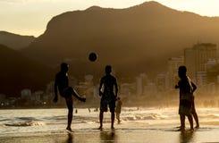 Uomo che gioca con la palla alla spiaggia Fotografia Stock