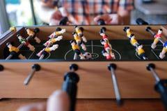 Uomo che gioca fine del gioco di calcio di calcio-balilla su con i suoi amici fotografia stock libera da diritti