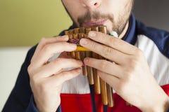Uomo che gioca flauto di Pan a casa fotografia stock