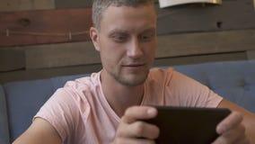 Uomo che gioca gioco sullo smartphone video d archivio