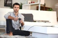 Uomo che gioca i video giochi da solo Fotografie Stock