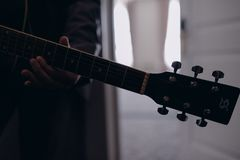 Uomo che gioca il primo piano della chitarra all'interno sulla foto fotografia stock libera da diritti