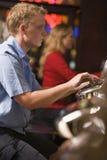 Uomo che gioca le slot machine Immagini Stock Libere da Diritti