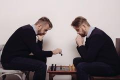 Uomo che gioca scacchi contro di se stesso fotografie stock