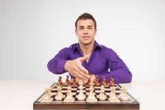 Uomo che gioca scacchi su fondo bianco Immagine Stock