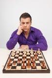 Uomo che gioca scacchi su fondo bianco Immagini Stock