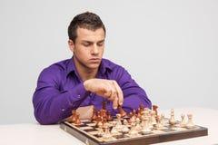 Uomo che gioca scacchi su fondo bianco Fotografia Stock