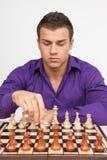 Uomo che gioca scacchi su fondo bianco Immagini Stock Libere da Diritti