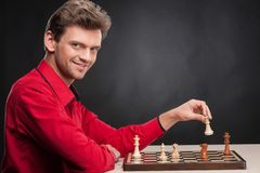 Uomo che gioca scacchi su fondo nero Fotografia Stock