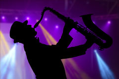 Uomo che gioca sul sassofono contro lo sfondo di bello lig Fotografia Stock