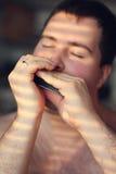 Uomo che gioca sull'armonica Fotografia Stock Libera da Diritti