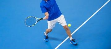 Uomo che gioca a tennis sul pavimento blu fotografia stock