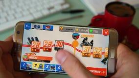 Uomo che gioca un video gioco sul suo Smartphone nell'ufficio video d archivio
