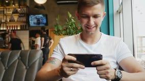 Uomo che gioca video gioco in caffè sulla dipendenza del telefono cellulare, dell'aggeggio o del gioco video d archivio