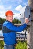 Uomo che gira l'interruttore di accensione in un impianto industriale Fotografia Stock
