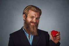 Uomo che giudica il contenitore di regalo a forma di del cuore rosso pronto per il San Valentino immagini stock libere da diritti