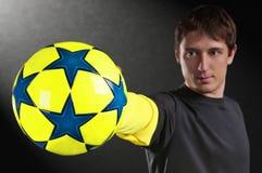 Uomo che giudica una sfera di calcio variopinta disponibila Immagini Stock