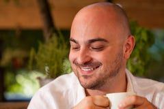 Uomo che gode del caffè con un sorriso Fotografia Stock