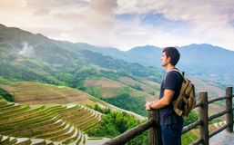 Uomo che gode del paesaggio asiatico sbalorditivo del terrazzo del riso immagini stock