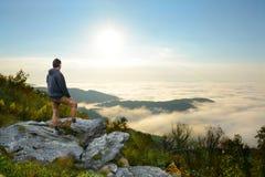Uomo che gode del paesaggio nebbioso della montagna all'alba Fotografie Stock