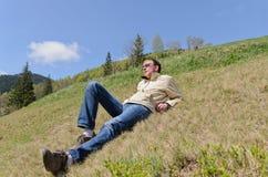 Uomo che gode del sole della montagna Immagini Stock