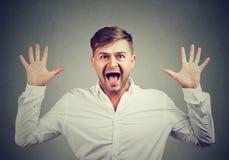 Uomo che grida alla macchina fotografica nella sorpresa immagini stock libere da diritti