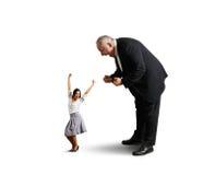 Uomo che grida alla piccola donna di affari allegra Fotografie Stock