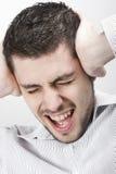 Uomo che grida e che copre le sue orecchie Immagini Stock