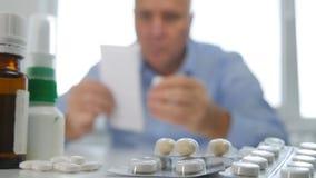 Uomo che guarda ad alcune pillole con una prescrizione medica a disposizione fotografie stock
