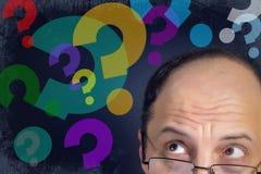Uomo che guarda ai punti interrogativi Fotografia Stock Libera da Diritti