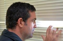Uomo che guarda attraverso i ciechi Fotografie Stock