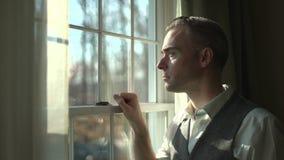 uomo che guarda fuori finestra dall'interno della stanza scura video d archivio