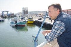 Uomo che guarda fuori sopra il porto Fotografia Stock