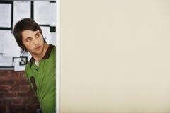 Uomo che guarda intorno all'angolo in ufficio Fotografie Stock