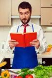 Uomo che guarda in libro di cucina Fotografia Stock